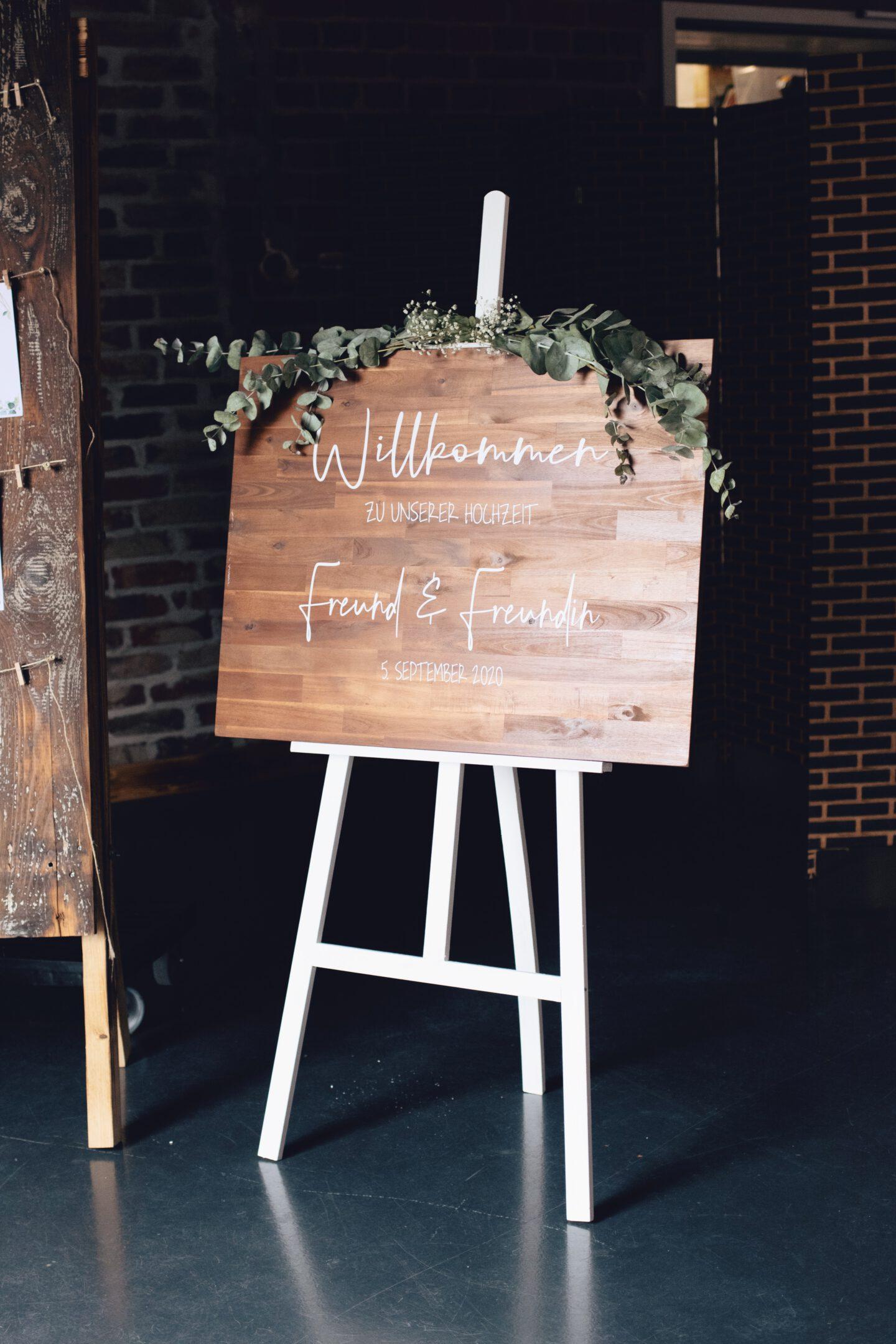 DIY Boho-Hochzeit: Willkommenschild aus Holz mit weißer Schrift