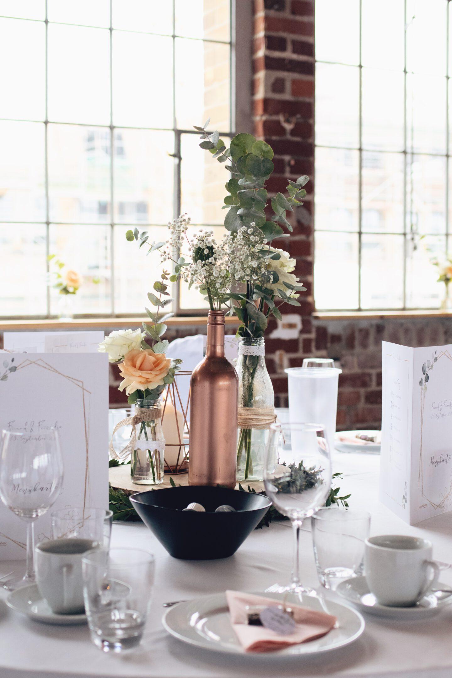 DIY Boho-Hochzeit: Deko mit Holzscheiben, kleinen Vasen, Kupferkerze und Eukalyptus